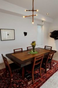 The dining table in the home has a Peter Zubiate light fixture hanging over it.